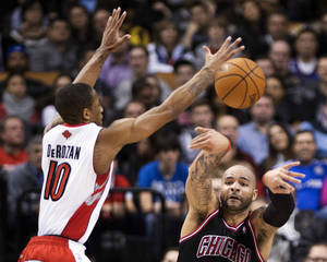 photo - Toronto Raptors forward DeMar DeRozan (10) tries to block a pass from Chicago Bulls forward Carlos Boozer, right, during the first half of their NBA basketball game, Wednesday, Jan. 16, 2013, in Toronto. (AP Photo/The Canadian Press, Nathan Denette)