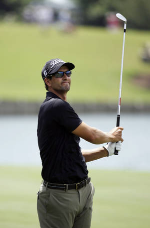 Photo - Adam Scott of Australia, reacts to his shot from the 18th fairway during the third round of The Players championship golf tournament at TPC Sawgrass, Saturday, May 10, 2014, in Ponte Vedra Beach, Fla. (AP Photo/John Raoux)