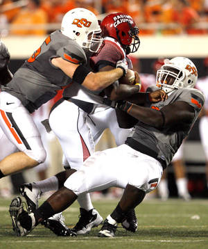 Photo - Oklahoma State's Caleb Lavey, left, and Anthony Rogers sack Louisiana-Lafayette's Blaine Gautier during the second half of the game Saturday. Photo by Sarah Phipps, The Oklahoman
