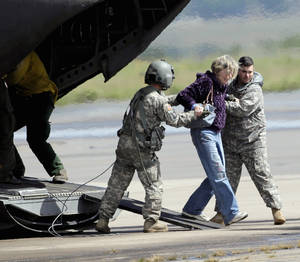 Photo - A woman is  helped off of a military helicopter at the Boulder Municipal Airport in Boulder, Colo., on on Monday,  Sept. 16,  2013, after being rescued. Thousands of people remained stranded by high water and washed out roads in the state. (AP Photo/Ed Andrieski)