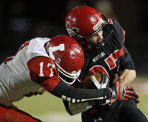 Photo -                    Lawton's Kalin Sadler tackles Mustang's Kale Harper during a game in 2012. Sadler, who is No. 28 on The Oklahoman's Super 30 recruiting list, has received a scholarship offer from New Mexico.                     Photo by Sarah Phipps, The Oklahoman