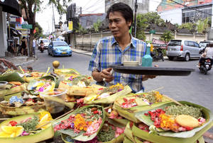 photo -   This Aug. 25, 2012 photo shows a Balinese man offering food to local god in Kuta, Bali, Indonesia. It can be hard to find Bali's serenity and beauty amid the villas with infinity pools and ads for Italian restaurants. But the rapidly developing island's simple pleasures still exist, in deserted beaches, simple meals of fried rice and coconut juice, and scenes of rural life. (AP Photo/Firdia Lisnawati)