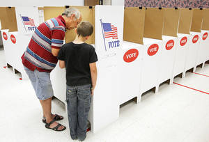 Photo - Xavier Gass, 9, of Choctaw, watches Monday as his grandfather, Jimmy R. Gass, also of Choctaw, marks his ballot in a booth during early voting at the Oklahoma County Election Board in Oklahoma City.  Photo by Paul B. Southerland, The Oklahoman