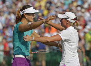 Photo - FILE - In this June 22, 2014, file photo, Michelle Wie, left, is embraced by runner-up Stacy Lewis after winning the U.S. Women's Open golf tournament in Pinehurst, N.C.  One is tall and powerful, the other compact and precise. Wie and Lewis, for all their differences, have become fast friends in golf. They're also leading an American revival, which resumes this week at Royal Birkdale. (AP Photo/Chuck Burton, File)