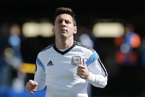 Photo - Argentina's Lionel Messi jogs during a training session at Itaquerao Stadium in Sao Paulo, Brazil, Monday, June 30, 2014. Argentina will face Switzerland in their next World Cup soccer match, Tuesday.  (AP Photo/Victor R. Caivano)