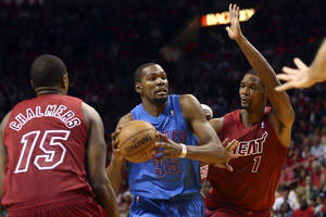 Photo - Miami Heat's Mario Chalmers (15) and Chris Bosh (1) defend against Oklahoma City Thunder's Kevin Durant during the second half of an NBA basketball game in Miami, Tuesday, Dec. 25, 2012. The Heat won 103-97. (AP Photo/J Pat Carter) ORG XMIT: FLJC113
