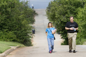 Photo - Christy Watson, communications director for the Foundation for Oklahoma City Public Schools, and schools Superintendent Karl Springer walk door to door, asking parents to enroll students in Thelma R. Parks Elementary School. PHOTO BY STEVE GOOCH, THE OKLAHOMAN <strong>Steve Gooch - The Oklahoman</strong>
