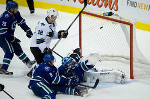 Photo - Vancouver Canucks' Mike Santorelli, left, Chris Tanev, bottom, goalie Roberto Luongo and San Jose Sharks' Patrick Marleau, 12, watch as the puck enters the net for the winning goal off the stick of Sharks' Dan Boyle, not seen, during overtime NHL hockey action in Vancouver, British Columbia, on Thursday Nov. 14, 2013. (AP Photo/The Canadian Press, Darryl Dyck)