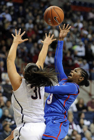 Photo - SMU's Gabrielle Wilkins (3) drives past Connecticut's Stefanie Dolson (31) during the first half of an NCAA college basketball game in Storrs, Conn., Tuesday, Feb. 4, 2014. (AP Photo/Fred Beckham)