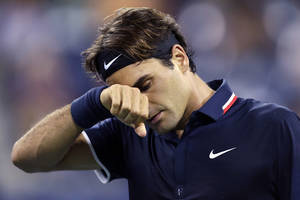 Photo -   Roger Federer, of Switzerland, wipes his brow late in the fourth set during his loss to Tomas Berdych, of the Czech Republic, in the quarterfinal round of play at the U.S. Open tennis tournament, Wednesday, Sept. 5, 2012, in New York. Berdych won 7-6 (1), 6-4, 3-6, 6-3. (AP Photo/Charles Krupa)