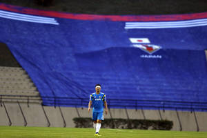 Photo - Japan's Shinji Okazaki walks in front of giant Japanese team uniform hanging in the stands during a training session in Sorocaba, Brazil, Sunday, June 8, 2014.  Japan plays in group C of the 2014 soccer World Cup. (AP Photo/Shuji Kajiyama)