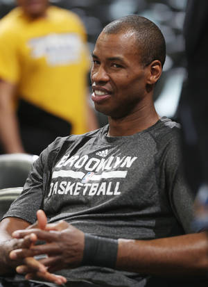 Photo - Brooklyn Nets center Jason Collins rests in a courtside seat after warming for the Nets' NBA basketball game against the Denver Nuggets in Denver on Thursday, Feb. 27, 2014. (AP Photo/David Zalubowski)