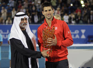 Photo - Novak Djokovic of Serbia, right, receives the winner's trophy from Sheikh Hamdan bin Mubarak Al Nahyan, UAE Minister of Higher Education and Scientific Research, after he beat David Ferrer of Spain during the final match of the Mubadala World Tennis Championship in Abu Dhabi, United Arab Emirates, Saturday, Dec. 28, 2013. (AP Photo/Kamran Jebreili)