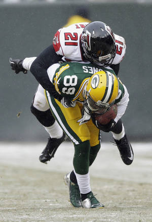 Photo - Atlanta Falcons' Desmond Trufant (21) tries to tackle Green Bay Packers' James Jones after a catch during the first half of an NFL football game Sunday, Dec. 8, 2013, in Green Bay, Wis. (AP Photo/Tom Lynn)