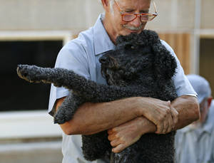 Photo - PRISON INMATES / DOGS: Bill Gassaway hugs Luke at the Lexington Assessment and Reception Center, Friday, July 11,  2013, in Lexington, Okla. Photo by Sarah Phipps, The Oklahoman