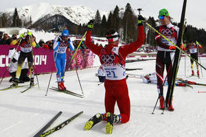 Photo - Switzerland's Dario Cologna, center, celebrates winning the the men's cross-country 30k skiathlon as, from left, Germany's Tobias Angerer, Italy's Giorgio  di Centa and Norway's Petter Northug look at the 2014 Winter Olympics, Sunday, Feb. 9, 2014, in Krasnaya Polyana, Russia. (AP Photo/Gregorio Borgia)