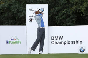 Photo - Golfer Tiger Woods watches his tee shot on the ninth hole during the pro-am round of the 2013 BMW Championship golf tournament at Conway Farms Golf Club in Lake Forest. Ill., Wednesday, Sept. 11, 2013. (AP Photo/Charles Rex Arbogast)