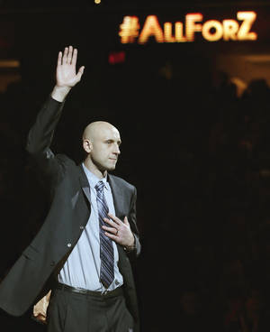 Photo - Zydrunas Ilgauskas is introduced during halftime of an NBA basketball game between the New York Knicks and the Cleveland Cavaliers on Saturday, March 8, 2014, in Cleveland. Soft-spoken and doggedly determined, Ilgauskas, who overcame serious injuries and personal tragedy to become one of Cleveland's best and most beloved players, had his No. 11 jersey retired Saturday night during an elaborate halftime ceremony certain to be emotionally poignant. (AP Photo/Tony Dejak)