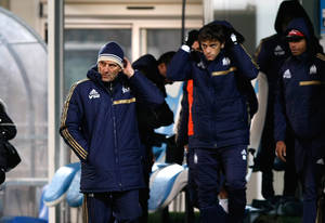 Photo - Marseille's French coach Elie Baup, left,  reacts with Marseille team members after losing against Nantes, at the end of  their League One soccer match , at the Velodrome Stadium, in Marseille, southern France, Friday, Dec. 6, 2013. (AP Photo/Claude Paris)