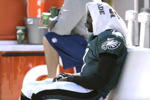 Photo - Philadelphia Eagles' Michael Vick (7) sits on the bench during the first half of an NFL football game against the New York Giants on Sunday, Oct. 27, 2013, in Philadelphia. (AP Photo/Michael Perez)