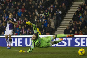 Photo - Liverpool's Luis Suarez, left, scores past Stoke's Jack Butland during their English Premier League soccer match at the Britannia Stadium, Stoke, England, Sunday Jan 12, 2014. (AP Photo/Jon Super)