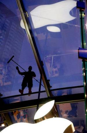 Photo - In this July 21, 2011 photo, a window washer works atop the cube-like structure of glass that houses the Apple Store showroom in the Upper West Side of Manhattan. Investors seem to think you want an iPad more than oil, as Apple Inc. became the most valuable company in the United States, surpassing Exxon Mobil Corp. on Wednesday. Apple briefly flirted with the top spot on Tuesday afternoon before settling back slightly below the oil giant. (AP Photo/Craig Ruttle) ORG XMIT: NYCR201
