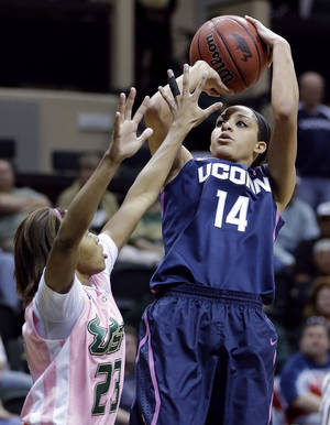 Photo - Connecticut guard Bria Hartley (14) shoots over South Florida guard Shalethia Stringfield (23) during the first half of an NCAA women's college basketball game, Sunday, Feb. 16, 2014, in Tampa, Fla. (AP Photo/Chris O'Meara)