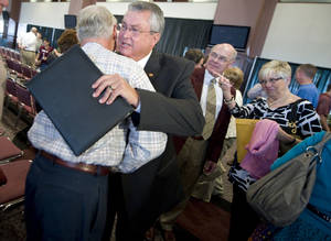 Photo -   Bill Byrne, second from left, gets a hug after announcing his retirement as athletic director at Texas A&M during a news conference in College Station, Texas, Tuesday, May 8, 2012. A&M won 45 Big 12 championships in 13 different sports under the 66-year-old Byrne. (AP Photo/College Station Eagle, Stuart Villanueva)