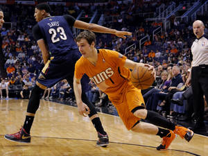 Photo - Phoenix Suns' Goran Dragic (1), of Slovenia, drives past New Orleans Pelicans' Anthony Davis during the second half of an NBA basketball game, Friday, Feb. 28, 2014, in Phoenix. The Suns won 116-104.(AP Photo/Matt York)