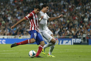 Photo - Real Madrid's Pepe from Brazil, right, duels for the ball with Atletico de Madrid's Diego Costa during a Spanish La Liga soccer match at the Santiago Bernabeu stadium in Madrid, Spain, Saturday, Sept. 28, 2013. (AP Photo/Daniel Ochoa de Olza)