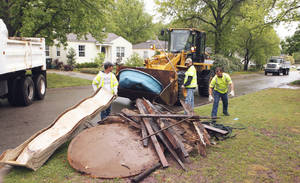 Photo - Sanitation workers pick up large trash items in front of a residence during a past spring cleanup campaign. OKLAHOMAN ARCHIVES