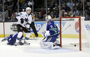 Photo - San Jose Sharks center Tomas Hertl (48) scores past Vancouver Canucks goalie Eddie Lack, right, during the first period of a preseason NHL hockey game on Tuesday, Sept. 24, 2013, in San Jose, Calif. (AP Photo/Marcio Jose Sanchez)