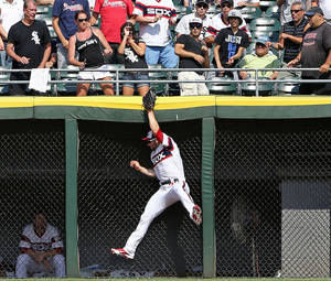 Photo - Chicago White Sox left fielder Casper Wells robs Atlanta Braves' Reed Johnson of a home run in the eighth inning as the White Sox defeated the Braves 3-1 in a baseball game in Chicago, Sunday, July 21, 2013. (AP Photo/Charles Cherney)