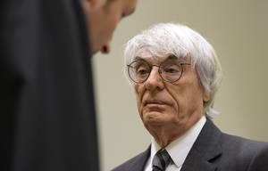 "Photo - Formula One boss Bernie Ecclestone, right, waits prior to the fourth day of his trial at the courthouse in Munich, southern Germany, Tuesday, May 13, 2014. Ecclestone is charged with bribery and incitement to breach of trust ""in an especially grave case"" over a US dollar 44 million payment to a German banker, that prosecutors allege was meant to facilitate the sale of the Formula One Group to a buyer of Ecclestone's liking. (AP Photo/Christof Stache, Pool)"