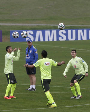 Photo - Brazil's soccer coach Luiz Felipe Scolari, top left, watches his players, including Neymar, left, practice at the Granja Comary training center in Teresopolis, Brazil, Wednesday, May 28, 2014. Brazil will host the World Cup soccer tournament that starts in June. (AP Photo/Hassan Ammar)