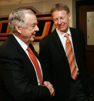 Photo - Boone Pickens (left) is congratulated by athletic director Mike Holder after the announcement of Picken's gift of $165 million to Oklahoma State University's athletic department in Stillwater, Oklahoma on Tuesday, January 10, 2006. by Steve Sisney/The Oklahoman <strong>STEVE SISNEY</strong>