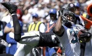 Photo - Jacksonville Jaguars running back Maurice Jones-Drew is tackled by Oakland Raiders cornerback Charles Woodson during the second quarter of an NFL football game, Sunday, Sept. 15, 2013, in Oakland, Calif. (AP Photo/Ben Margot)