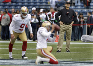 Photo - San Francisco 49ers head coach Jim Harbaugh, right, watches as San Francisco 49ers kicker Phil Dawson (9) and holder Andy Lee warm up before a NFL football game against the Seattle Seahawks, Sunday, Sept. 15, 2013, in Seattle. (AP Photo/Elaine Thompson)
