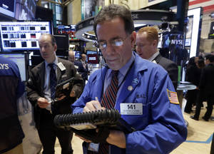 Photo - Trader Sal Suarino works on the floor of the New York Stock Exchange, Friday, Feb. 21, 2014. U.S. stocks are inching higher in early trading, putting the Standard & Poor's 500 index on track for its third straight week of gains. (AP Photo/Richard Drew)