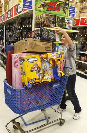 Photo - Shopper Shelly Church balances her cart at Toys R Us in Oklahoma City on Black Friday in 2011. Photo by Steve Gooch, The Oklahoman <strong></strong>