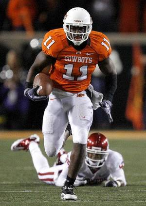 Photo - Oklahoma State's Shaun Lewis (11) returns an interception for a touchdown as Oklahoma's Ryan Broyles (85) misses a tackle during the Bedlam college football game between the University of Oklahoma Sooners (OU) and the Oklahoma State University Cowboys (OSU) at Boone Pickens Stadium in Stillwater, Okla., Saturday, Nov. 27, 2010. Photo by Sarah Phipps, The Oklahoman <strong>SARAH PHIPPS</strong>