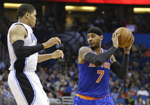 Photo - New York Knicks' Carmelo Anthony (7) looks to pass the ball around Orlando Magic's Tobias Harris, left, in the first half of an NBA basketball game in Orlando, Fla., Monday, Dec. 23, 2013. (AP Photo/John Raoux)