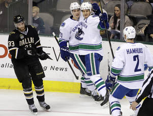 photo - Dallas Stars' Alex Goligoski (33) skates away as Vancouver Canucks' Mason Raymond (21), Kevin Bieksa (3) and Dan Hamhuis (2) celebrate Bieksa's second-period goal against the Dallas Stars in an NHL hockey game, Thursday, Feb. 21, 2013, in Dallas. The Canucks won 4-3. (AP Photo/Tony Gutierrez)