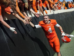 photo - Oklahoma State's J.W. Walsh (4) celebrates with fans after a college football game between Oklahoma State University (OSU) and Iowa State University (ISU) at Boone Pickens Stadium in Stillwater, Okla., Saturday, Oct. 20, 2012. OSU won, 31-10. Photo by Nate Billings, The Oklahoman