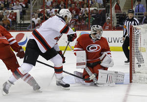 Photo - New Jersey Devils' Dainius Zubrus, left, of Lithuania, scores against Carolina Hurricanes' goalie Anton Khudobin, of Kazakhstan, during the first period of an NHL hockey game in Raleigh, N.C., Saturday, April 5, 2014. (AP Photo/Gerry Broome)
