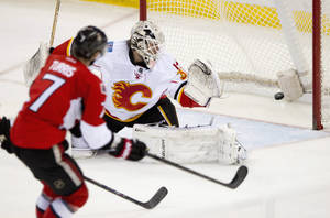 Photo - Ottawa Senators Kyle Turris scores on Calgary Flames goalie Karri Ramo during second period NHL action Sunday March 30, 2014 in Ottawa, Ontario. (AP Photo/The Canadian Press, Adrian Wyld)