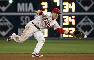 Photo - Philadelphia Phillies second baseman Chase Utley chases down a ground ball hit by Chicago Cubs' John Baker during the fourth inning of a baseball game, Friday, June 13, 2014, in Philadelphia. Baker was out on the play. (AP Photo/Matt Slocum)