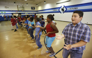 photo - Fifth-grade students at Highland Park Elementary School sing a presidential election rap song in Del City on Friday.