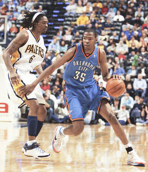 Photo - The Thunder's Kevin Durant, right, drives past Pacers guard Marquis Daniels during action Monday in Indinanpolis. Durant scored 37 points in the loss.AP photo