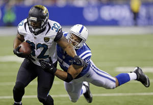 Photo - Jacksonville Jaguars' Maurice Jones-Drew (32) is tackled by Indianapolis Colts' Josh McNary (57) during the second half of an NFL football game on Sunday, Dec. 29, 2013, in Indianapolis. (AP Photo/Michael Conroy)